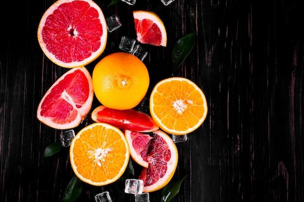 木製の黒い背景にオレンジとグレープフルーツジュース