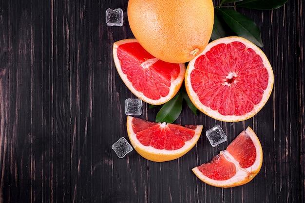 나무 검정색 배경에 오렌지와 자몽 주스