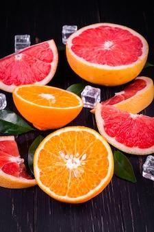 オレンジとグレープフルーツジュース木製の黒い背景に