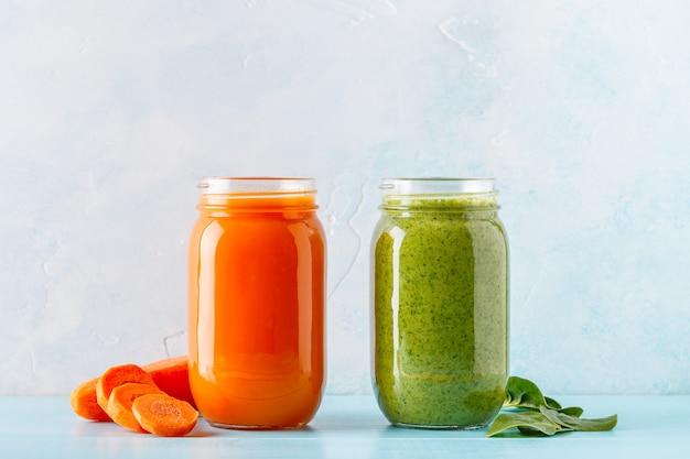 分離された瓶の中のオレンジと緑の色のスムージー