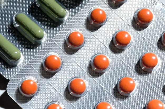 フォイルブリスターのオレンジと緑の錠剤は、明るい背景にあります。大きなiplan。上からの眺め