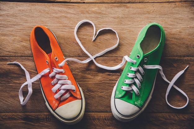 ハートスタイルのロープが付いたオレンジとグリーンのスニーカー。 -バレンタインデーの愛の概念