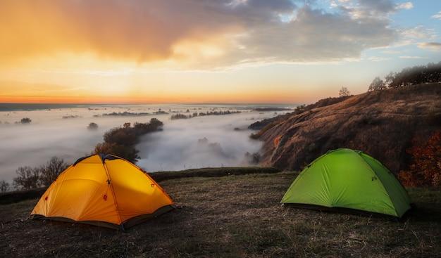 Оранжевые и зеленые палатки над рекой, укрытые туманом