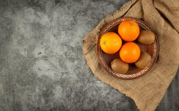 Апельсин и киви в гончарной посуде. вид сверху.