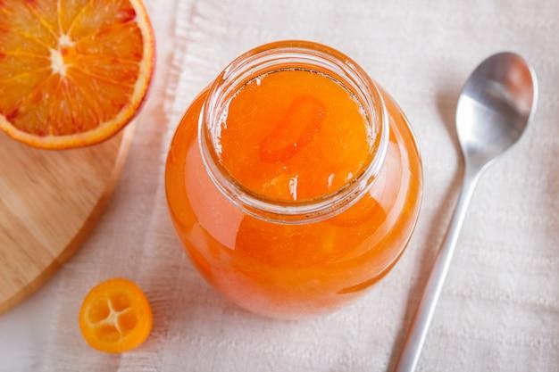 Апельсиново-кумкватовое варенье в стеклянной банке со свежими фруктами на белой льняной скатерти.