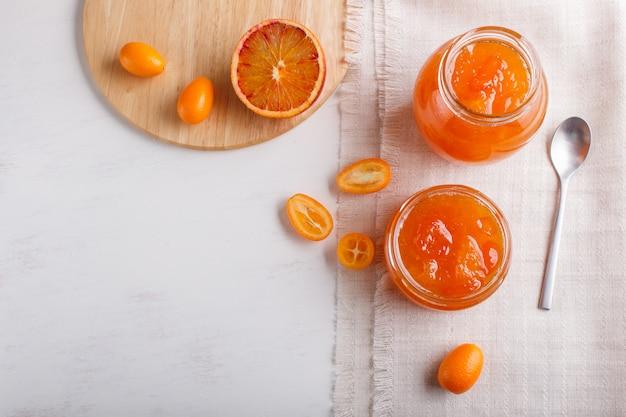 白の新鮮な果物とガラスの瓶にオレンジとキンカンのジャム