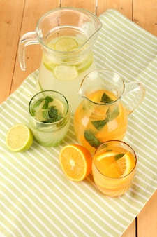 Апельсин и лимонад в кувшинах и стаканах на деревянном столе крупным планом