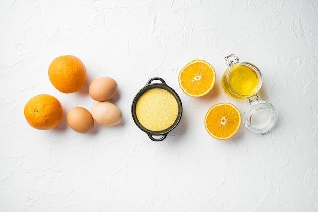 폴렌타 재료가 포함된 오렌지 및 만다린 케이크, 계란과 꿀 세트, 흰색 돌 테이블 배경, 위쪽 전망 플랫 레이, 텍스트 복사 공간