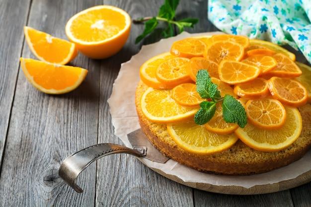 古い木の表面に逆さまにした、ポレンタのオレンジとマンダリンのケーキ。選択と集中。