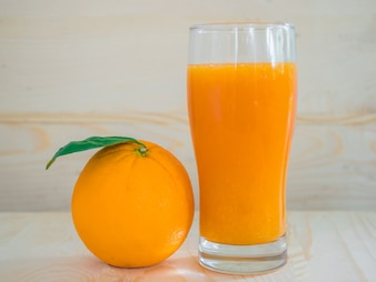 Orange and orange juice on wooden background.