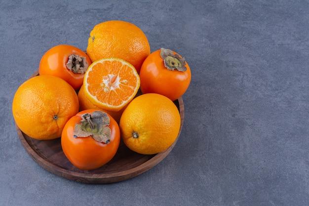 Апельсин и хурма на деревянной тарелке на мраморном столе.