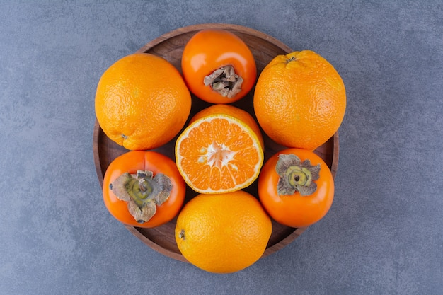 暗い表面の木製プレートにオレンジと柿