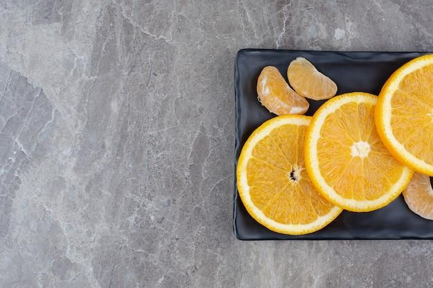 Ломтики апельсина и мандарина на черной тарелке.