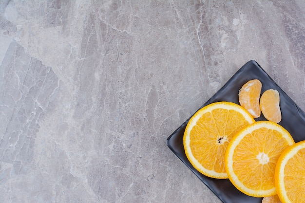 검정 잉크 판에 오렌지와 귤 조각입니다.
