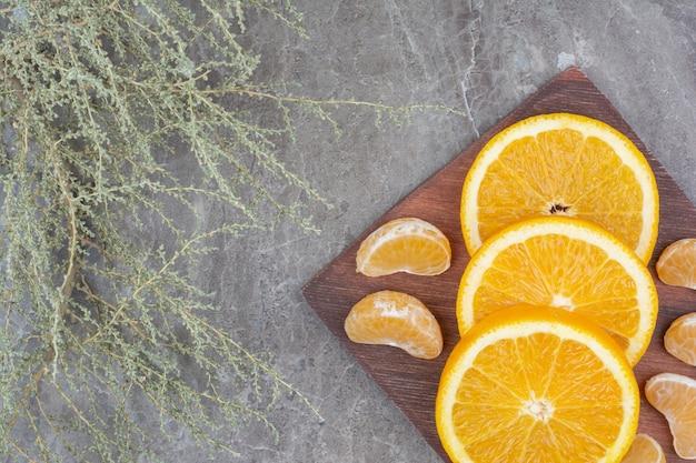 Ломтики апельсина и мандарина на деревянной доске.