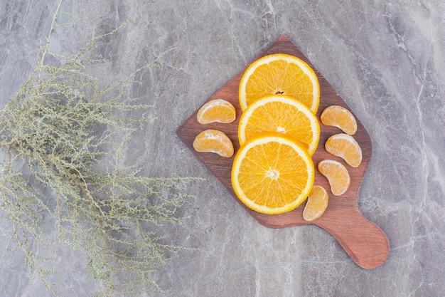 나무 보드에 오렌지와 귤 조각입니다.
