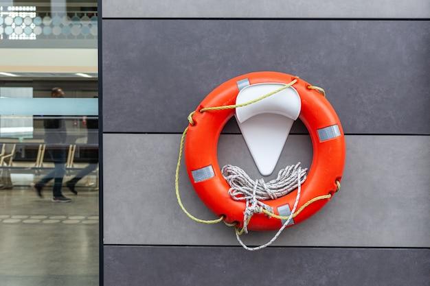 Оранжевый и белый спасательный круг, висящий на стене на морской