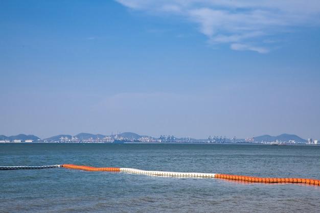 Оранжевые и белые пластиковые буи в море.