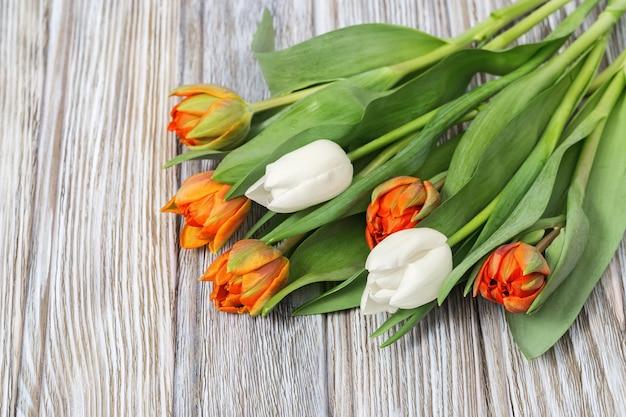Оранжевые и белые цветы тюльпана на старых деревянных