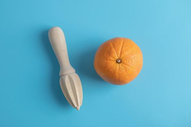 青いテーブルの上のオレンジと木製のリーマー。