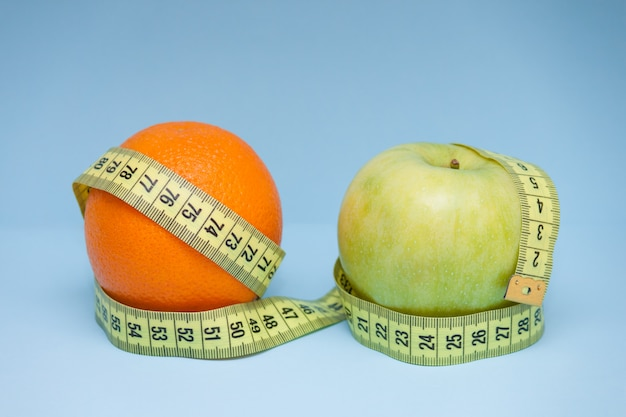 Orange and apple with measuring tape wrapped around them on the blue background.