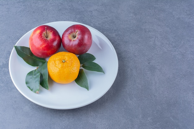 Orange and apples with leaves on plate on the dark surface