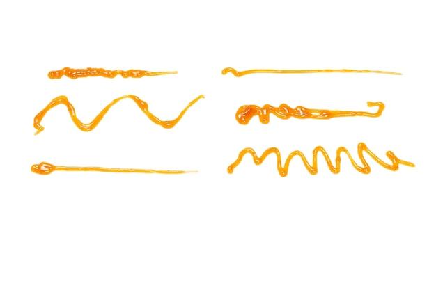 Orange apricot jam splashes isolated on white background. top view.