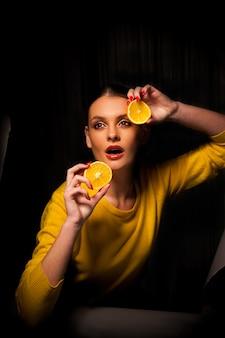 ビタミンc、健康食品、予防、免疫システムの供給源としてのオレンジ。オレンジスライスを保持している美しい女性