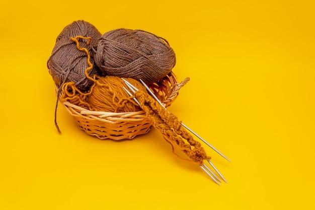 バスケットで編むためのオレンジ色の背景、茶色と黄土色の糸、針で編み始めた横