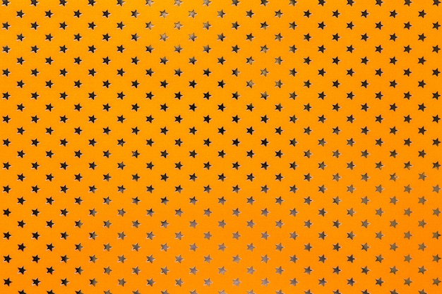 Orange background from metal foil paper with a golden stars pattern