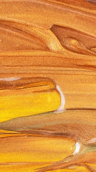 Оранжевый фон с блестящими мазками. абстрактная текстура. креативные мазки золотой краской