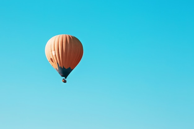 Orange balloon soars against the blue sky
