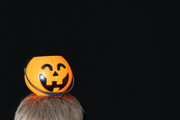 Orange basket in the shape of a pumpkin with a grinning face, jack's lantern on a child's head isolated on black background. waiting for halloween candies. happy halloween concept