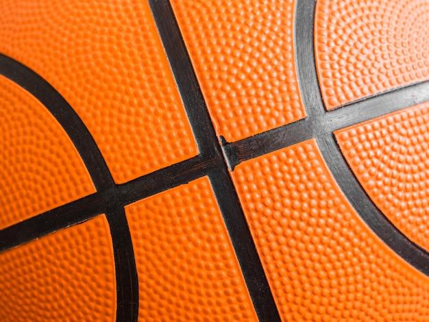 オレンジのバスケットボールのボールをクローズアップ。フラグメント、ブラックストライプ、テクスチャ。