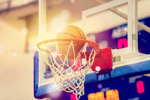 バスケットボールのフープに飛んでいるオレンジ色のバスケットボールボール