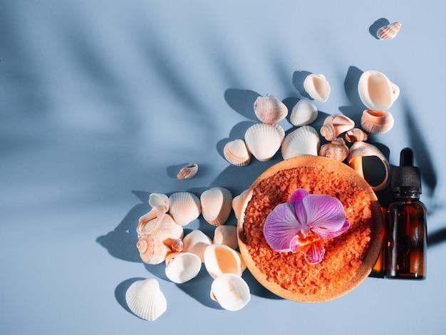 Оранжевая соль для ванн в блюдце с раковинами и цветок на синем фоне с тенью от тропического растения. copyspace, flatlay. спа, отдых, лето
