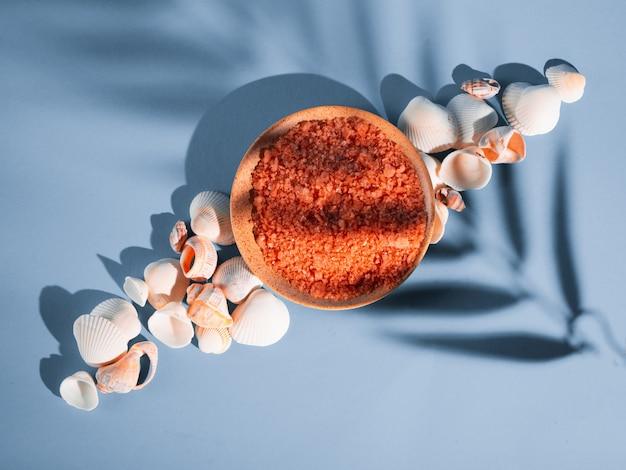 Оранжевая соль для ванн в блюдце с раковинами на синем фоне с тенью от тропического растения. copyspace, flatlay. спа, отдых, лето