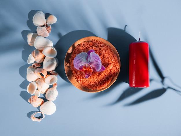 Оранжевая соль для ванн в блюдце с раковинами, красная свеча и цветок на синем фоне с тенью от тропического растения. copyspace, flatlay. спа, отдых, лето