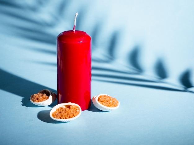 Оранжевая соль для ванн в блюдце с раковинами, красная свеча на синем фоне с тенью от тропического растения. copyspace. спа, отдых, лето