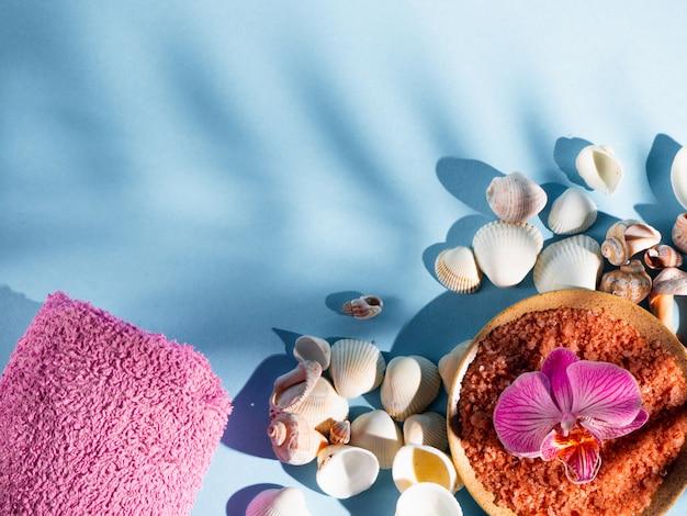 Оранжевая соль для ванн в блюдце с раковинами, полотенцем и цветком на синем фоне с тенью от тропического растения. copyspace, flatlay. спа, отдых, лето