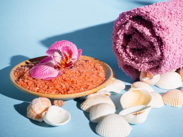Оранжевая соль для ванн в блюдце с раковинами, полотенцем и цветком на синем фоне с тенью от тропического растения. copyspace. спа, отдых, лето