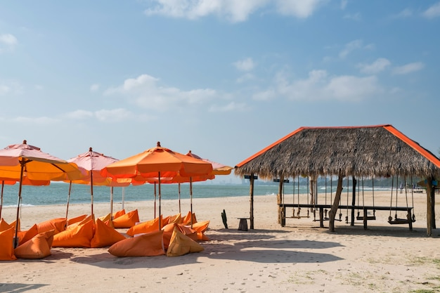 차암 해변, 펫차부리에서 푸른 하늘이 있는 바다 해변의 오렌지 빈백 좌석과 파라솔