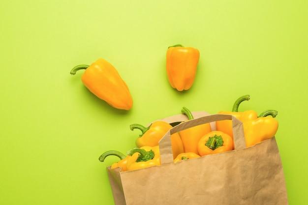 Оранжевый болгарский перец в бумажном пакете на зеленом фоне. вегетарианская пища. плоская планировка.