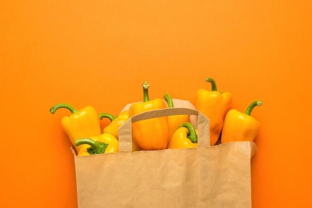 Оранжевый болгарский перец в бумажном пакете на оранжевом фоне. вегетарианская пища. свежий урожай овощей.