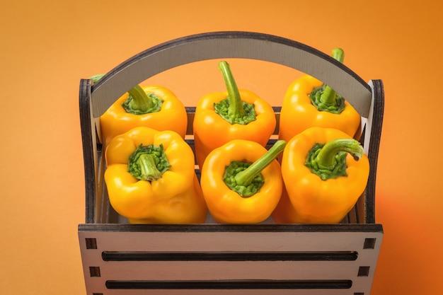 Оранжевый болгарский перец в деревянной коробке на оранжевом фоне. вегетарианская пища.