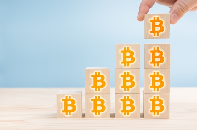 階段が上がると並んでいる木製のブロックにオレンジ色のビットコインのサイン。ビットコインbtc価格の上昇。ビットコインの成長