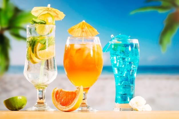 Orange blue drinks in glasses and sliced orange lime white flower