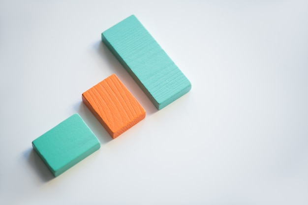 Orange and blue flat wooden bricks making up chart against white background with copyspace surrounding them