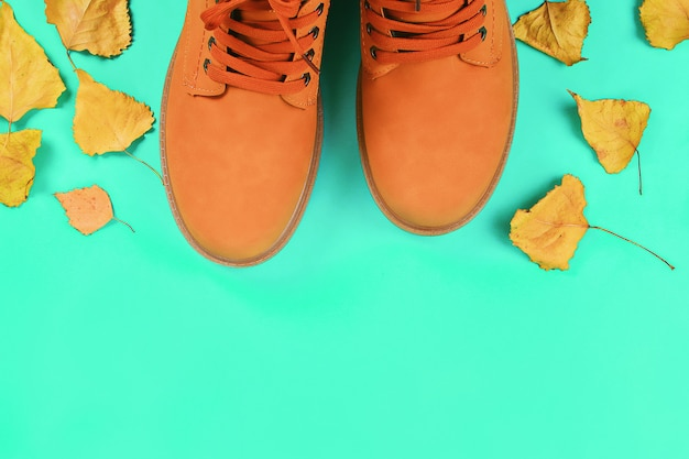 Orange boots among autumn leaves