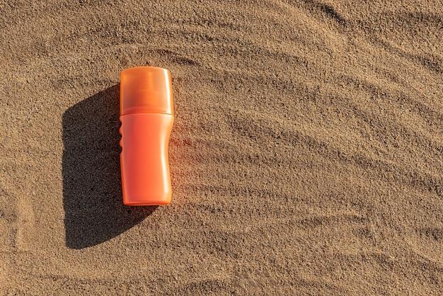 日焼け止めやローション用のオレンジ色のボトル。砂の上に黒い影のあるコンテナ。休暇中の夏。